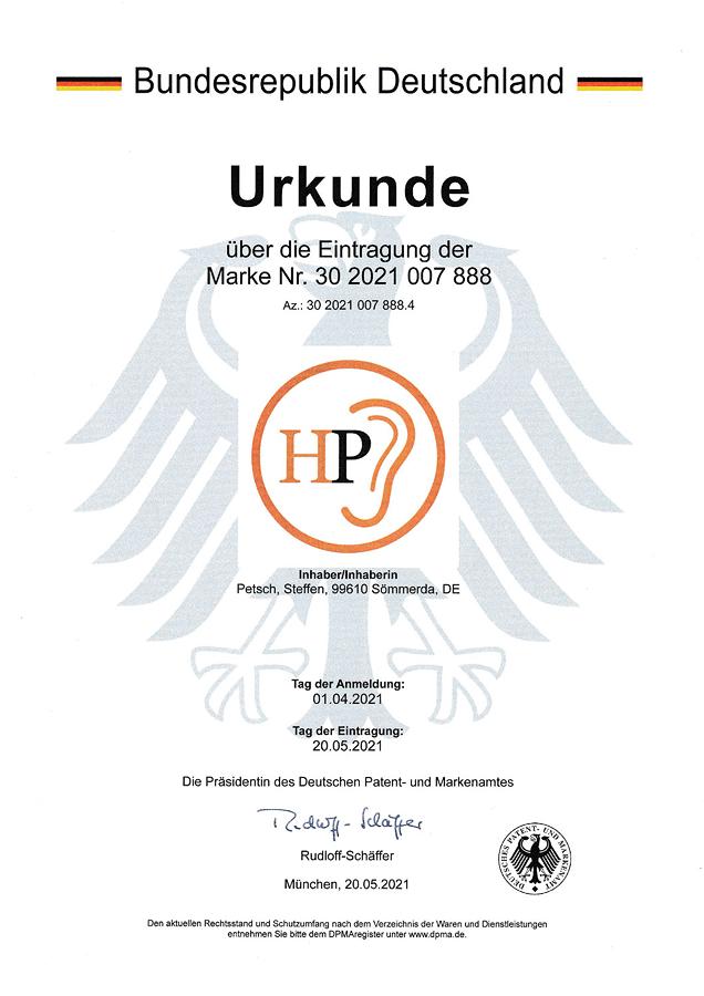 Urkunde Patent- und Markenamt - Hörakustik Petsch - Logo orange schwarz rund